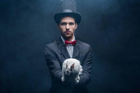 Photo pour Magicien confiant en costume et chapeau tenant lapin blanc, chambre sombre avec fumée - image libre de droit