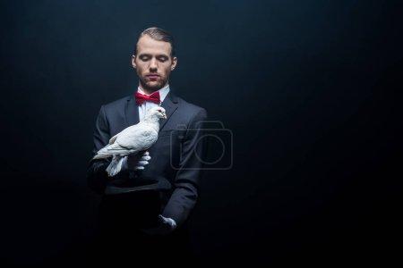 Photo pour Un jeune magicien montrant un truc avec une colombe et un chapeau dans une pièce sombre avec de la fumée - image libre de droit