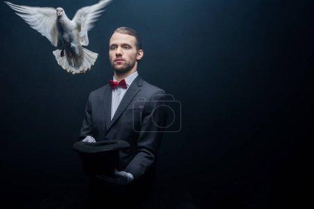 Photo pour Jeune magicien montrant tour avec colombe, baguette et chapeau dans la chambre noire avec de la fumée - image libre de droit
