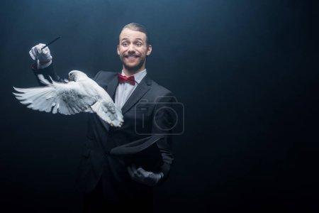 Photo pour Magicien souriant montrant tour avec colombe, baguette et chapeau dans la pièce sombre avec de la fumée - image libre de droit