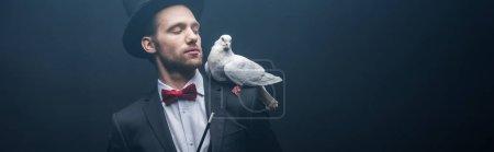 Photo pour Plan panoramique de colombe assise sur l'épaule du magicien en chapeau avec baguette dans une pièce sombre avec fumée - image libre de droit