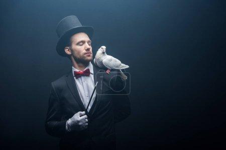 Photo pour Colombe assise sur l'épaule du magicien en chapeau avec baguette dans une pièce sombre avec fumée - image libre de droit
