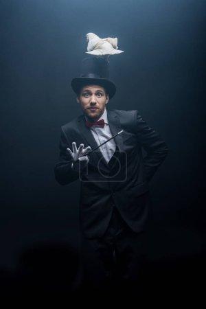 Photo pour Magicien émotionnel dans un chapeau avec baguette magique colombe dans une pièce sombre avec fumée - image libre de droit