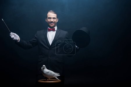 Photo pour Magicien heureux montrant tour avec colombe, baguette et chapeau dans la pièce sombre avec de la fumée - image libre de droit