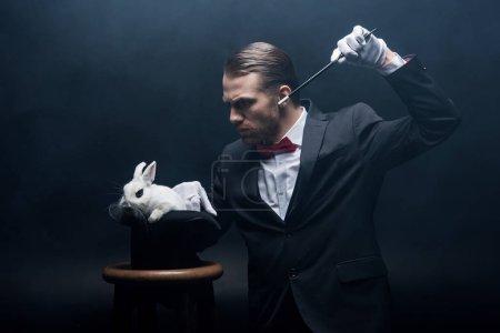 Photo pour Magicien concentré en costume montrant tour avec baguette et lapin blanc dans le chapeau, chambre sombre avec fumée - image libre de droit