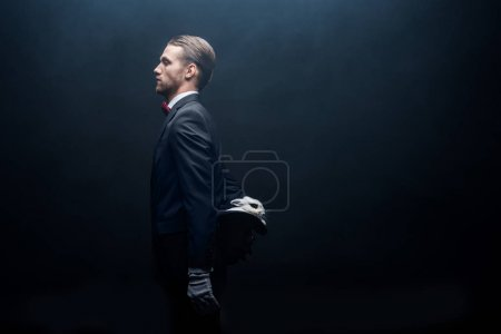 Photo for Side view of professional magician holding white rabbit in hat, dark room with smoke - Royalty Free Image