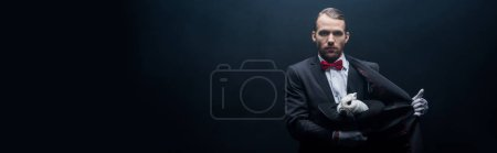 Photo for Panoramic shot of professional magician holding white rabbit in hat, dark room with smoke - Royalty Free Image