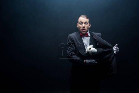 Photo pour Magicien choqué tenant un lapin blanc en chapeau, chambre noire avec fumée - image libre de droit