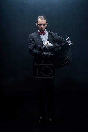 Photo pour Magicien professionnel en costume tenant le lapin blanc dans le chapeau, chambre sombre avec fumée - image libre de droit