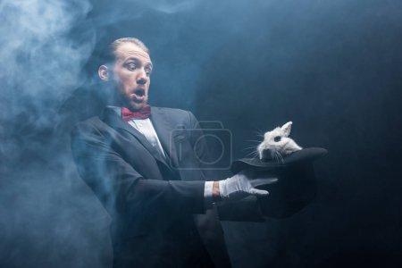 Photo pour Magicien effrayé tenant un lapin blanc en chapeau, chambre noire avec fumée - image libre de droit