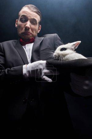 Photo pour Magicien confus tenant le lapin blanc dans le chapeau, chambre sombre avec de la fumée - image libre de droit