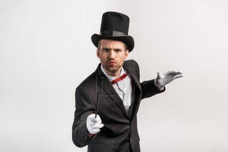 Photo pour Magicien inquiet en costume et chapeau tenant baguette, isolé sur gris - image libre de droit