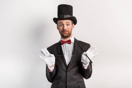 Photo pour Magicien adulte avec geste haussant les épaules tenant la baguette, sur gris - image libre de droit
