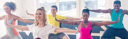 Photo pour Photo panoramique de danseurs multiethniques souriants jouant de la zumba dans un studio de danse - image libre de droit