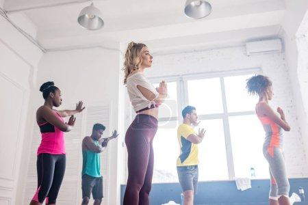 Foto de Vista de bajo ángulo de los bailarines multiculturales que realizan movimientos zumba en el estudio de danza. - Imagen libre de derechos