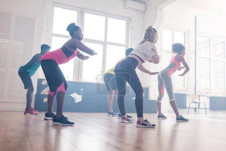 Foto de Vista lateral de jóvenes bailarines multiculturales entrenando movimientos zumba en el estudio de danza. - Imagen libre de derechos