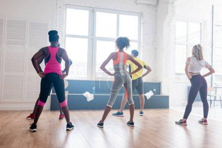 Photo pour Vue arrière de danseurs de zumba multiethniques s'entraînant ensemble dans un studio de danse - image libre de droit