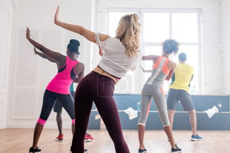 Photo pour Back view of multiethnic zumba dancers performing movements in dance studio - image libre de droit