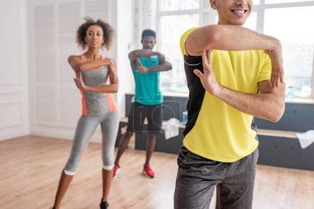 Photo pour Concentration sélective d'un entraîneur souriant pratiquant la zumba avec des danseurs afro-américains dans un studio de danse - image libre de droit