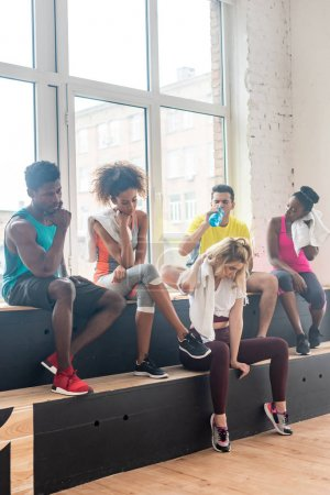 Photo for Multicultural zumba dancers resting while training in dance studio - Royalty Free Image