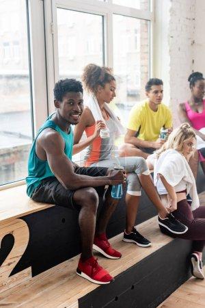 Foto de Enfoque selectivo del hombre afroamericano con botella deportiva sonriendo a la cámara por bailarines multiculturales en el banco en el estudio de danza - Imagen libre de derechos