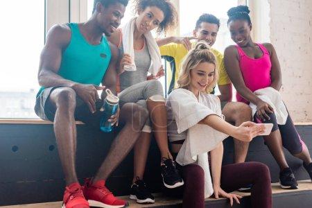 Foto de Bailarines de zumba multiculturales sonrientes tomando selfie mientras descansan en el banco en el estudio de danza - Imagen libre de derechos