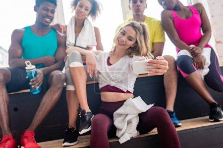 Photo pour Focus sélectif de danseurs de zumba multiculturels prenant des sélections tout en se reposant sur un banc dans un studio de danse - image libre de droit