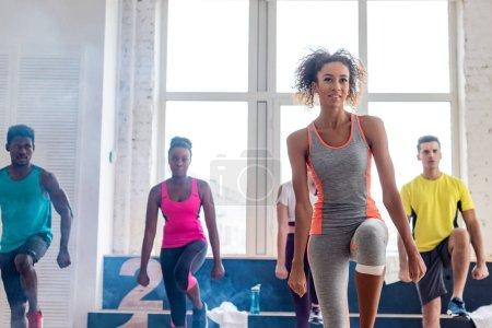 Foto de Enfoque selectivo de los movimientos afriamericanos de aprendizaje de zumba con bailarines multiculturales en estudio de danza con humo. - Imagen libre de derechos