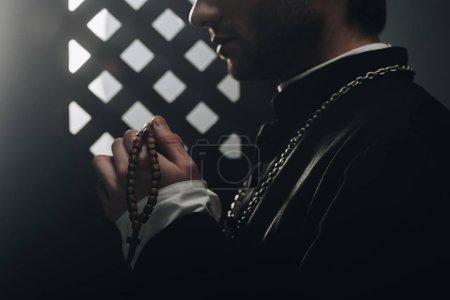 Photo pour Vue partielle du prêtre catholique tenant des perles de chapelet en bois près de la grille confessionnelle dans l'obscurité avec des rayons de lumière - image libre de droit