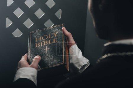 vista recortada del sacerdote católico sosteniendo la sagrada Biblia cerca de la rejilla confesional en la oscuridad con rayos de luz