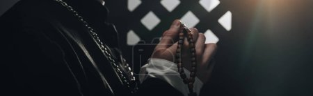 Photo for Partial view of catholic priest holding wooden rosary beads near confessional grille in dark with rays of light, panoramic shot - Royalty Free Image