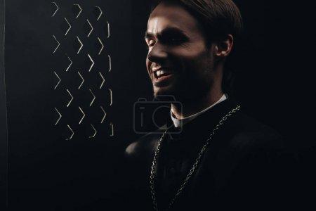 Photo pour Jeune prêtre catholique sarcastique riant près de la calandre confessionnelle dans l'obscurité avec des rayons de lumière - image libre de droit