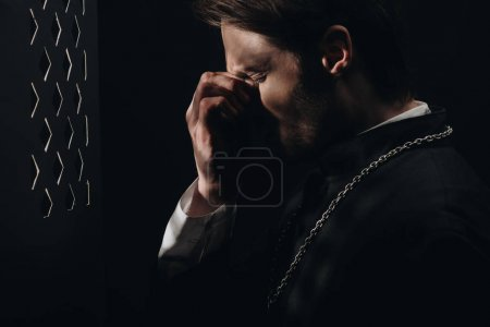 Photo for Young tense catholic priest touching face with closed eyes near confessional grille in dark with rays of light - Royalty Free Image