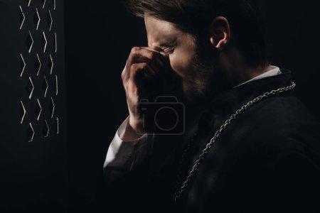 Photo pour Jeune prêtre catholique tendu touchant le visage avec les yeux fermés près de la calandre confessionnelle dans l'obscurité avec des rayons de lumière - image libre de droit