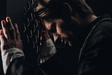 Photo pour Jeune prêtre catholique tendu les yeux fermés appuyé sur la calandre confessionnelle dans l'obscurité avec des rayons de lumière - image libre de droit