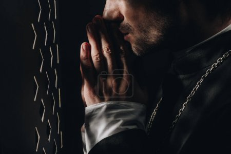 Photo for Cropped view of catholic priest praying near confessional grille in dark with rays of light - Royalty Free Image