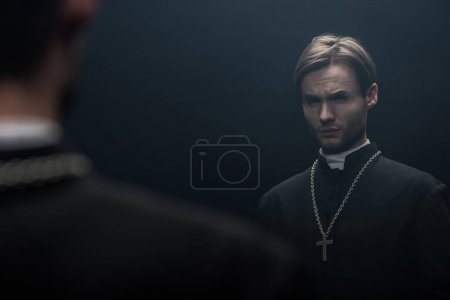 Photo pour Jeune prêtre catholique tendu regardant son propre reflet isolé sur noir - image libre de droit