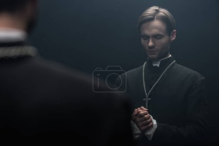 Photo for Young serious catholic priest praying with closed eyes near own reflection isolated on black - Royalty Free Image