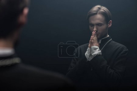 Photo pour Young serious catholic priest praying with closed eyes near own reflection isolated on black - image libre de droit