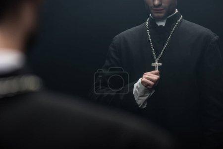 Photo pour Vue recadrée du prêtre catholique touchant croix sur son collier près de son propre reflet isolé sur noir - image libre de droit