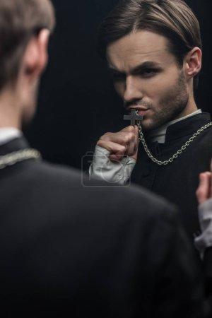 Photo pour Jeune prêtre catholique tendu embrassant sainte croix en regardant sa propre réflexion isolée sur le noir - image libre de droit