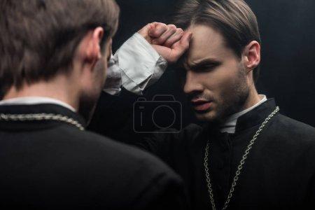 Photo pour Jeune prêtre catholique tendu tenant le poing près du front tout en se tenant près de son propre reflet isolé sur noir - image libre de droit