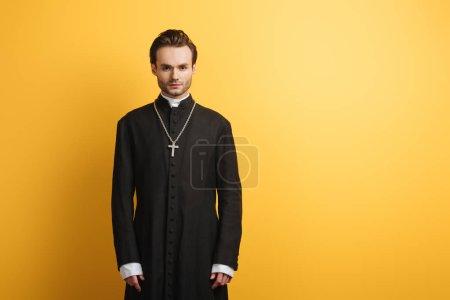 Photo pour Jeune prêtre catholique confiant regardant la caméra tout en se tenant isolé sur jaune - image libre de droit