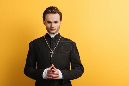 Photo pour Sérieux prêtre catholique debout avec les mains serrées tout en regardant la caméra isolée sur jaune - image libre de droit