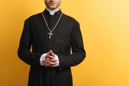 Photo pour Vue recadrée du prêtre catholique debout avec les mains serrées isolées sur jaune - image libre de droit