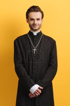 Photo pour Jeune prêtre catholique souriant à la caméra tout en se tenant isolé sur jaune - image libre de droit