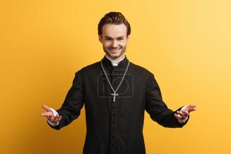 Photo pour Prêtre catholique souriant debout à bras ouverts et souriant isolé sur jaune - image libre de droit