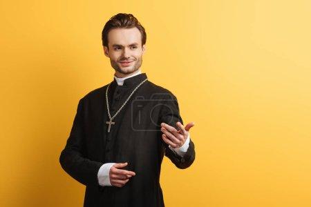 Photo pour Prêtre catholique souriant debout avec la main tendue tout en regardant loin isolé sur jaune - image libre de droit