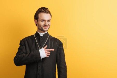 Photo pour Prêtre catholique souriant regardant caméra et pointant du doigt isolé sur jaune - image libre de droit