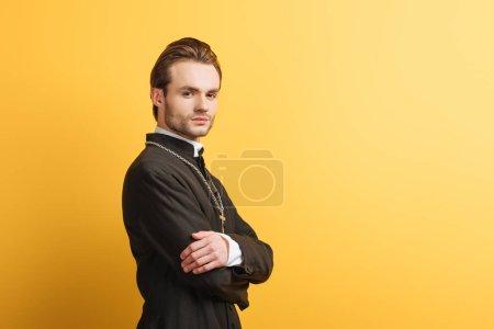 Photo pour Confiant prêtre catholique aux bras croisés regardant la caméra isolée sur jaune - image libre de droit